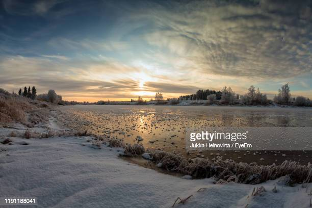 scenic view of snow covered landscape against sky during sunset - heinovirta stock photos and pictures