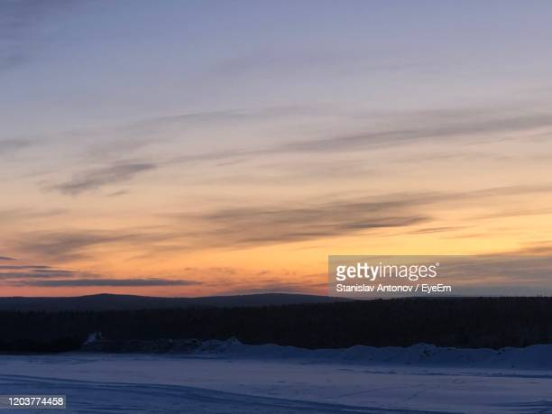 scenic view of snow covered landscape against sky during sunset - antonov stock pictures, royalty-free photos & images