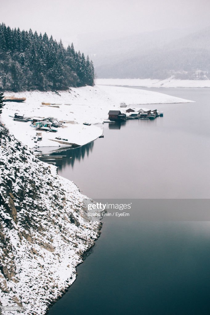 Scenic View Of Snow Covered Landscape By Lake : Stock Photo