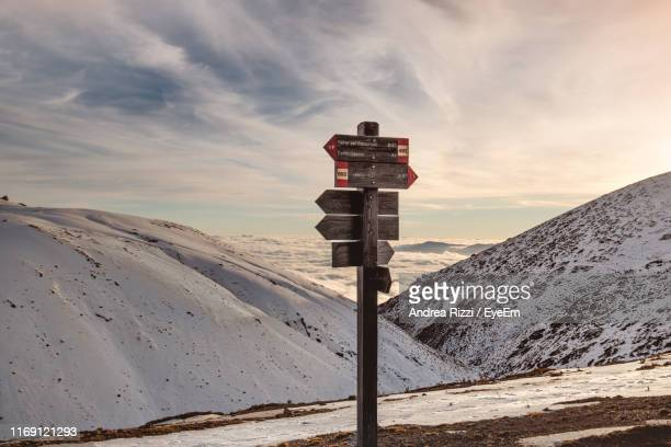 scenic view of snow covered mountain against sky - andrea rizzi stockfoto's en -beelden