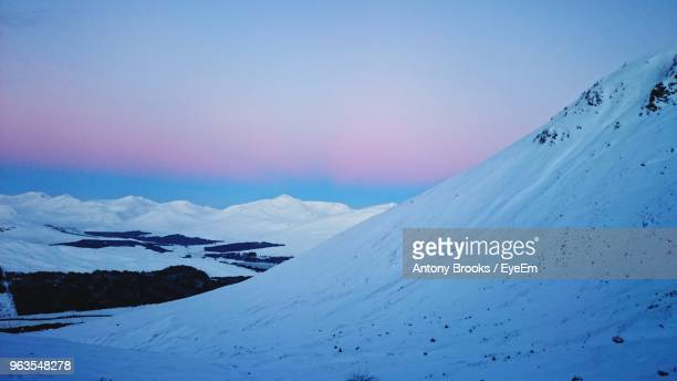 scenic view of snow covered mountain against sky - snow scene stock photos and pictures