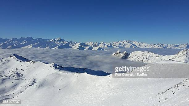 scenic view of snow covered mountains against clear blue sky - trois vallees stock photos and pictures