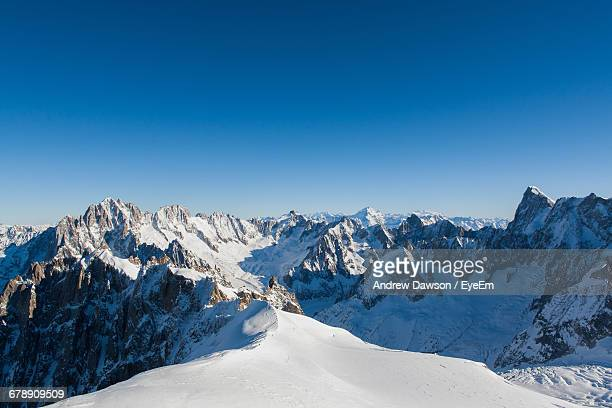 scenic view of snow covered mountains against clear sky - sneeuwkap stockfoto's en -beelden