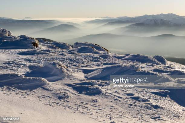 Scenic View Of Snow Covered Mountains Against Sky over the Clouds