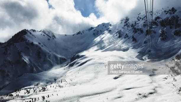 scenic view of snow covered mountains against sky - 富山県 ストックフォトと画像