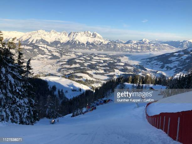 scenic view of snow covered mountains against sky - kitzbuehel stock-fotos und bilder