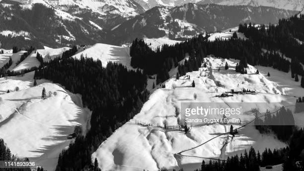scenic view of snow covered mountains - sandra gygax stock-fotos und bilder