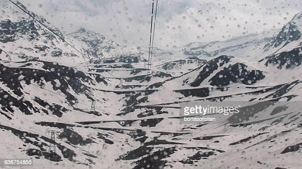 scenic view of snow covered mountains seen through glass - bortes stockfoto's en -beelden