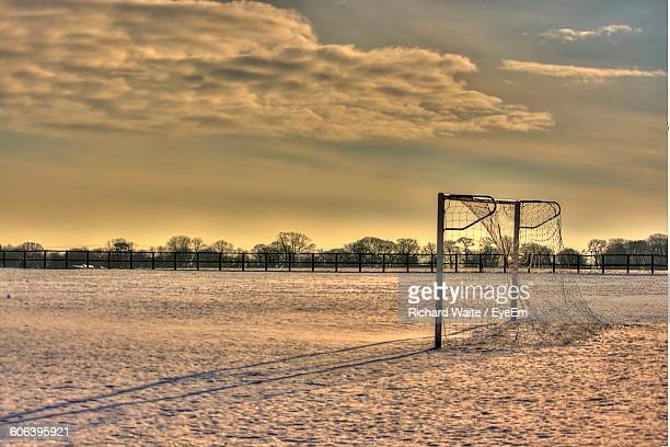 Scenic View Of Snow Covered Soccer Field Against Sky During Sunset