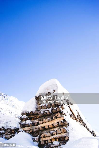 Scenic View Of Snow Covered Stack Of Logs