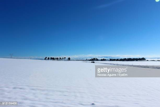 Scenic View Of Snow Field Against Clear Blue Sky