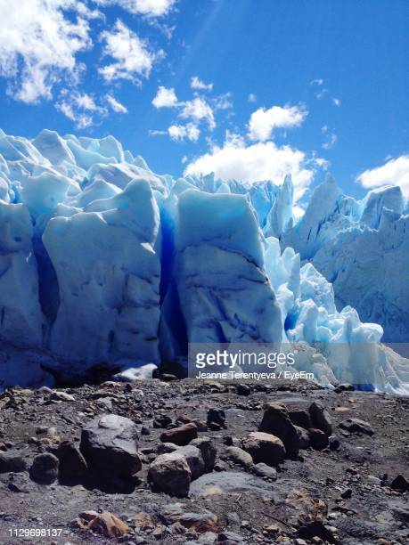 Scenic View Of Snow Through Rocks Against Blue Sky
