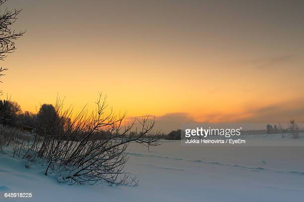 scenic view of snowcapped landscape against orange sky - heinovirta stock photos and pictures