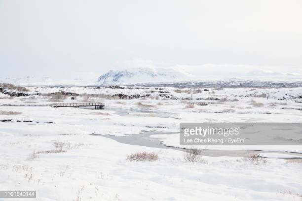 scenic view of snowcapped landscape against sky - thingvellir national park stock photos and pictures
