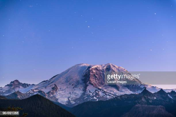scenic view of snowcapped mountain against blue sky at dusk - mt rainier stock pictures, royalty-free photos & images