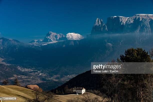 scenic view of snowcapped mountain against blue sky - loibl stock-fotos und bilder