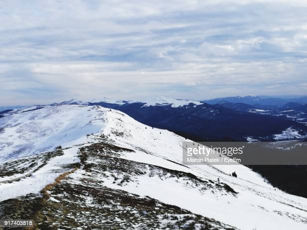 scenic view of snowcapped mountain against cloudy sky - piatek stock-fotos und bilder