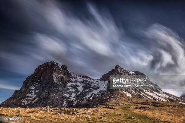 scenic view of snowcapped mountain against sky - andrea rizzi foto e immagini stock