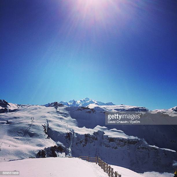 scenic view of snowcapped mountain range against blue sky - chauvin stock pictures, royalty-free photos & images