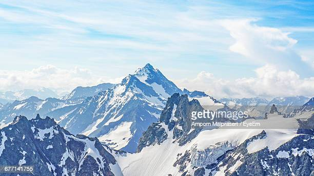 Scenic View Of Snowcapped Mountain Range Against Cloudy Sky