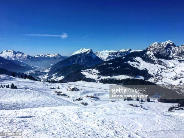 scenic view of snowcapped mountains against blue sky - ルグランボルナン ストックフォトと画像