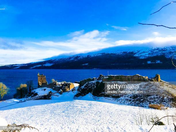 scenic view of snowcapped mountains against blue sky - drumnadrochit stock pictures, royalty-free photos & images