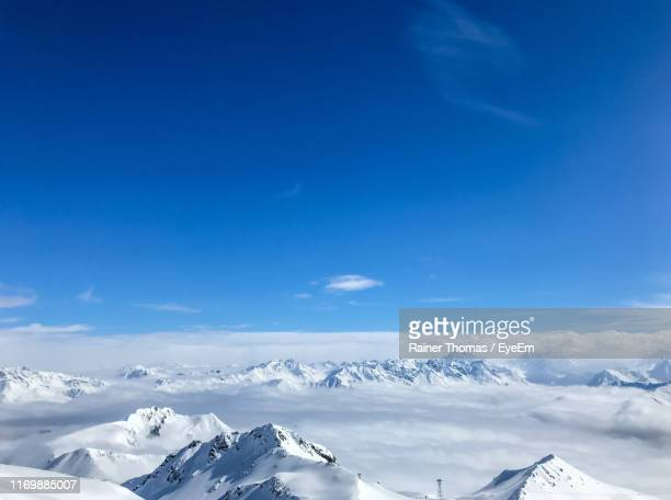 scenic view of snowcapped mountains against blue sky - davos stock-fotos und bilder