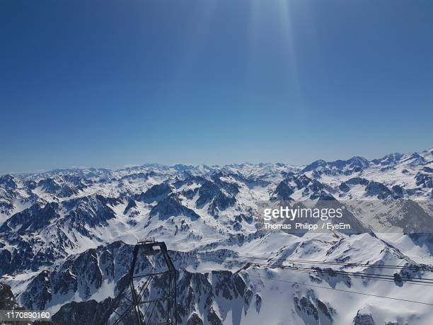 scenic view of snowcapped mountains against blue sky - バニェールドビゴール ストックフォトと画像