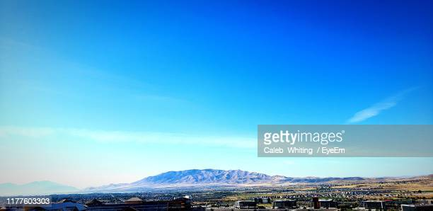 scenic view of snowcapped mountains against blue sky - lehi foto e immagini stock