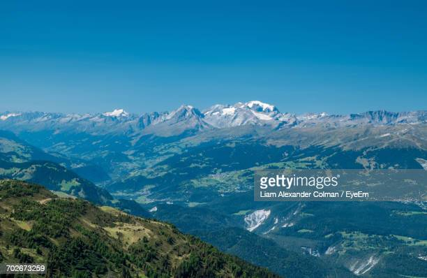 scenic view of snowcapped mountains against blue sky - colman stock photos and pictures