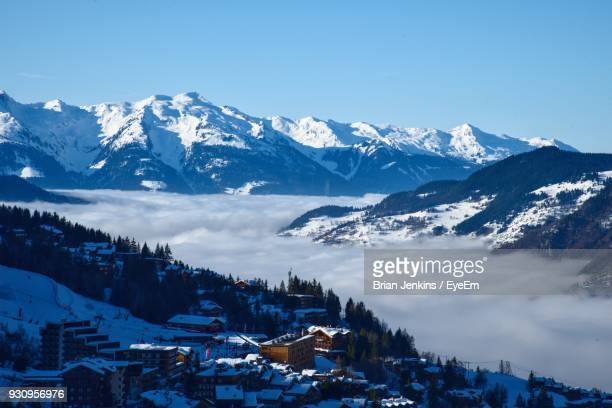 scenic view of snowcapped mountains against blue sky - courchevel stock pictures, royalty-free photos & images