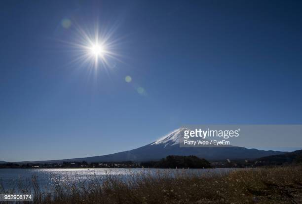 scenic view of snowcapped mountains against blue sky - 太陽の光 ストックフォトと画像