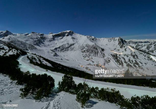 scenic view of snowcapped mountains against clear blue night sky - principality of liechtenstein stock pictures, royalty-free photos & images