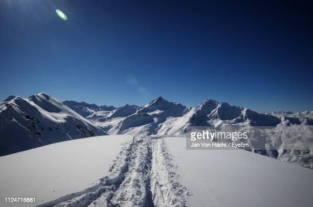 scenic view of snowcapped mountains against clear blue sky - davos stock-fotos und bilder