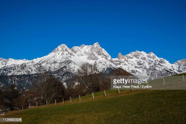 scenic view of snowcapped mountains against clear blue sky - saalfelden stock pictures, royalty-free photos & images