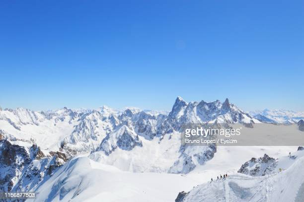 scenic view of snowcapped mountains against clear blue sky - deep snow stock pictures, royalty-free photos & images