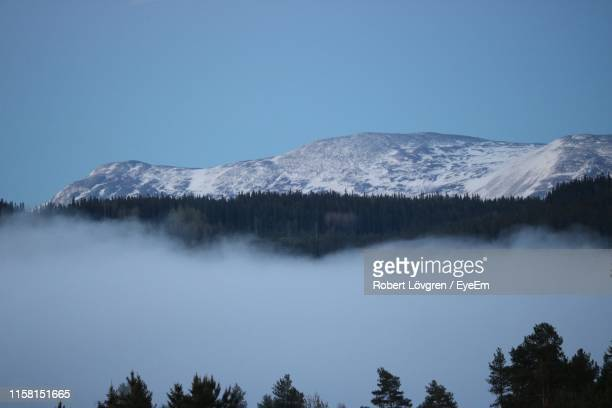 scenic view of snowcapped mountains against clear blue sky - östersund stock-fotos und bilder