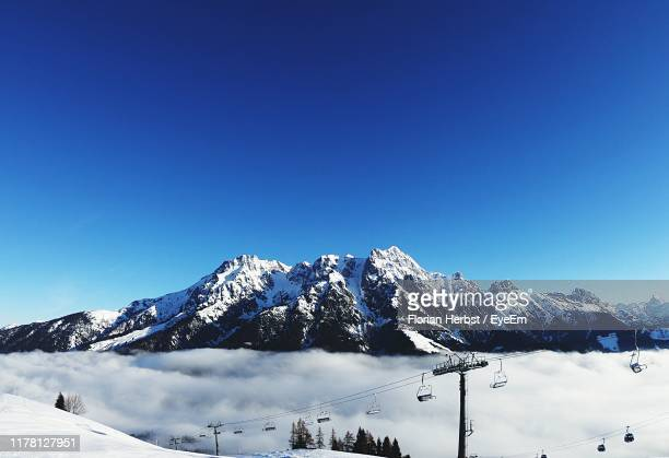 scenic view of snowcapped mountains against clear blue sky - leogang stock pictures, royalty-free photos & images