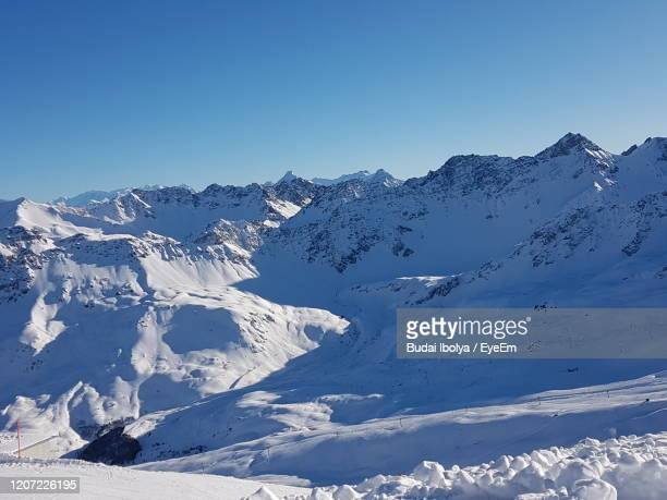 scenic view of snowcapped mountains against clear blue sky - アロサ ストックフォトと画像