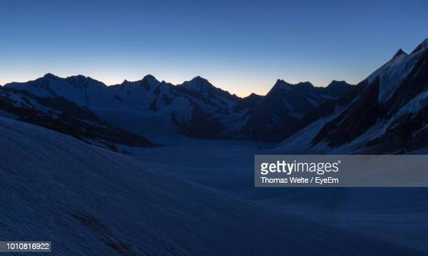 scenic view of snowcapped mountains against clear sky during sunset - dämmerung stock-fotos und bilder