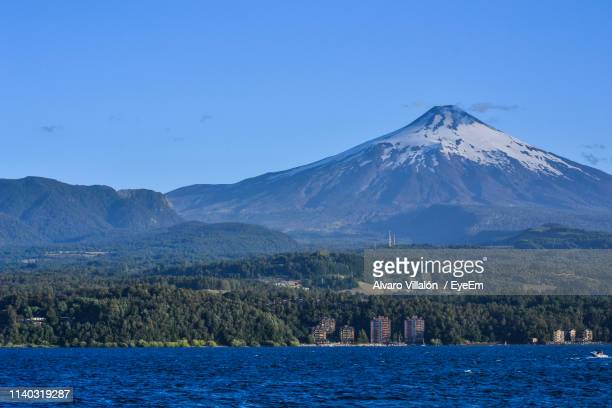 scenic view of snowcapped mountains against clear sky - villarrica stock photos and pictures