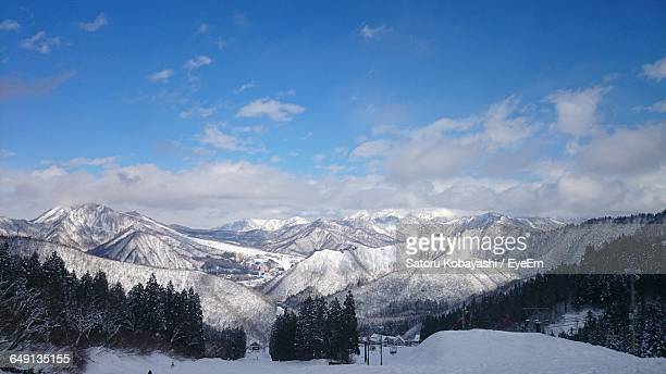 Scenic View Of Snowcapped Mountains Against Cloudy Blue Sky On Sunny Day