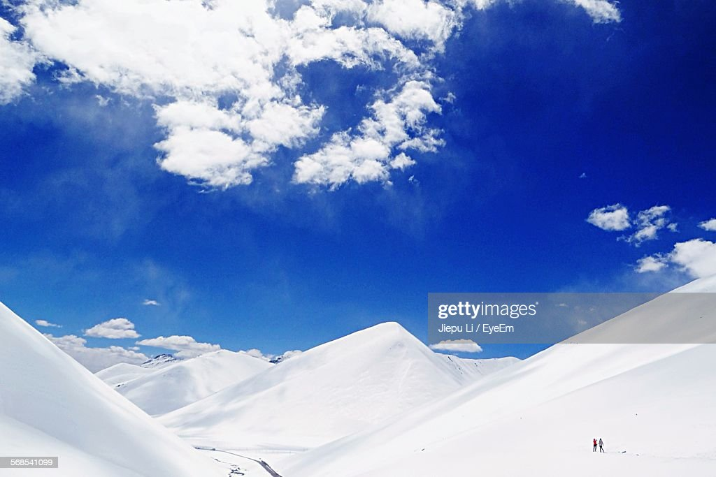 Scenic View Of Snowcapped Mountains Against Cloudy Blue Sky : Stock Photo