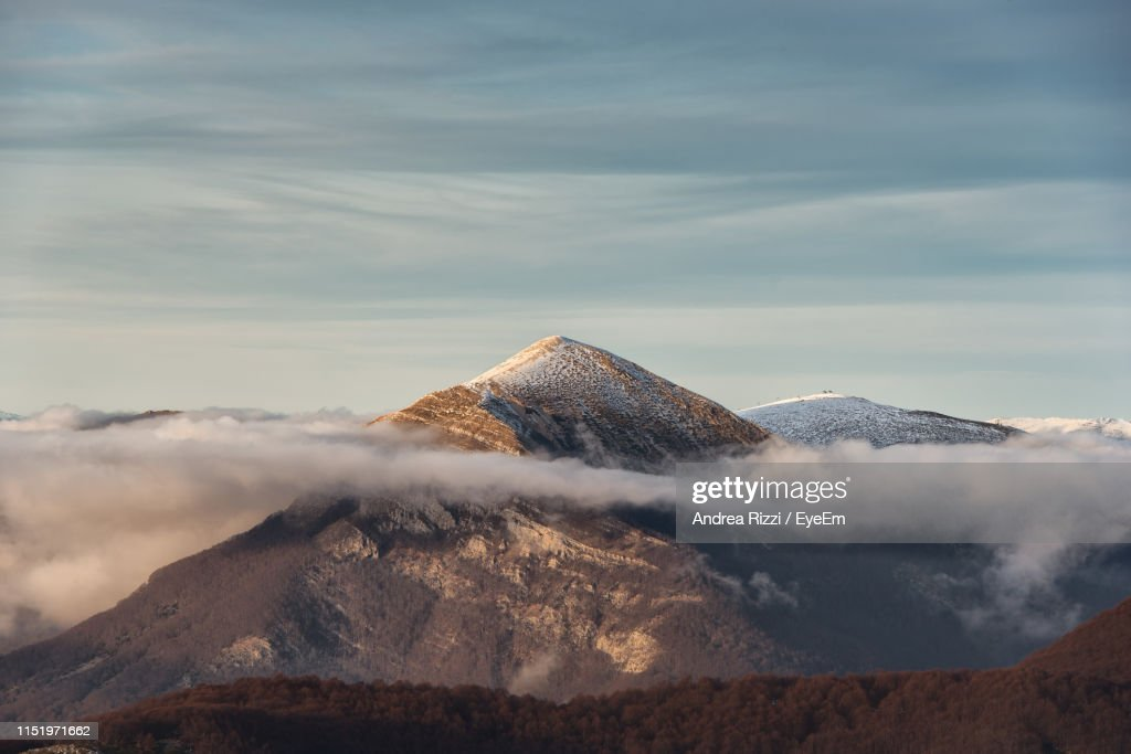 Scenic View Of Snowcapped Mountains Against Cloudy Sky During Sunset : Stock Photo