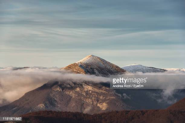 scenic view of snowcapped mountains against cloudy sky during sunset - andrea rizzi stockfoto's en -beelden