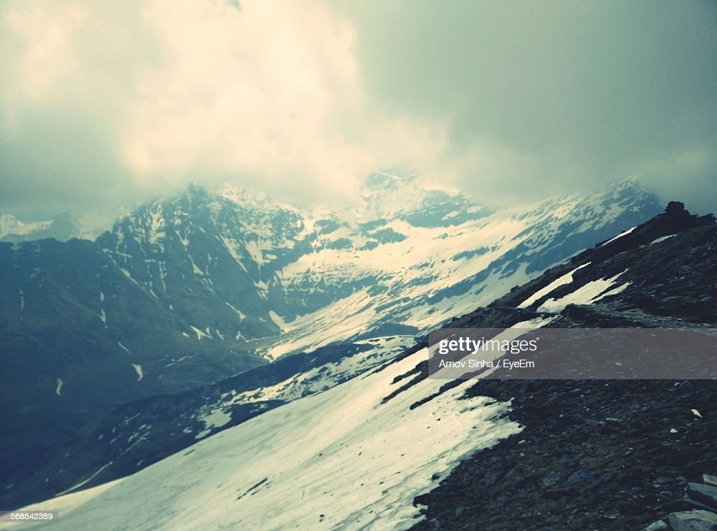 Scenic View Of Snowcapped Mountains Against Cloudy Sky : Stock Photo