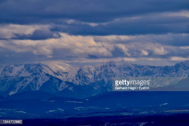 scenic view of snowcapped mountains against dramatic sky - gerhard hagn stock-fotos und bilder