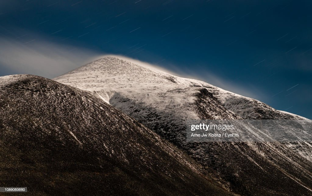 Scenic View Of Snowcapped Mountains Against Sky At Night : Stock Photo