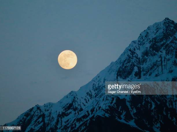 scenic view of snowcapped mountains against sky at night - snow moon stock pictures, royalty-free photos & images
