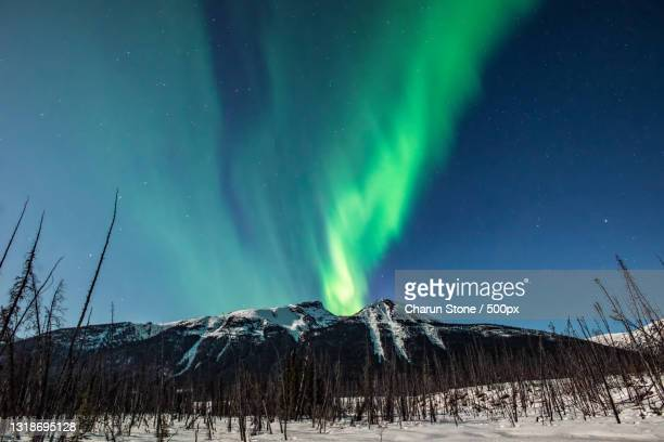 scenic view of snowcapped mountains against sky at night,yukon unorganized,yukon,canada - canada stock pictures, royalty-free photos & images